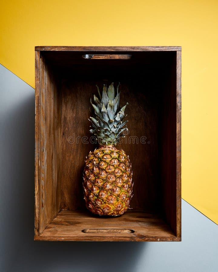 Opinión plana de la endecha de la fruta jugosa madura de la piña en una caja vieja del vintage de madera en fondo del gris del am imagen de archivo libre de regalías