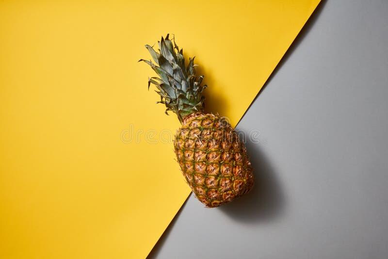 Opinión plana de la endecha de la fruta tropical de la piña sola en un fondo amarillo-gris del duotone imagenes de archivo