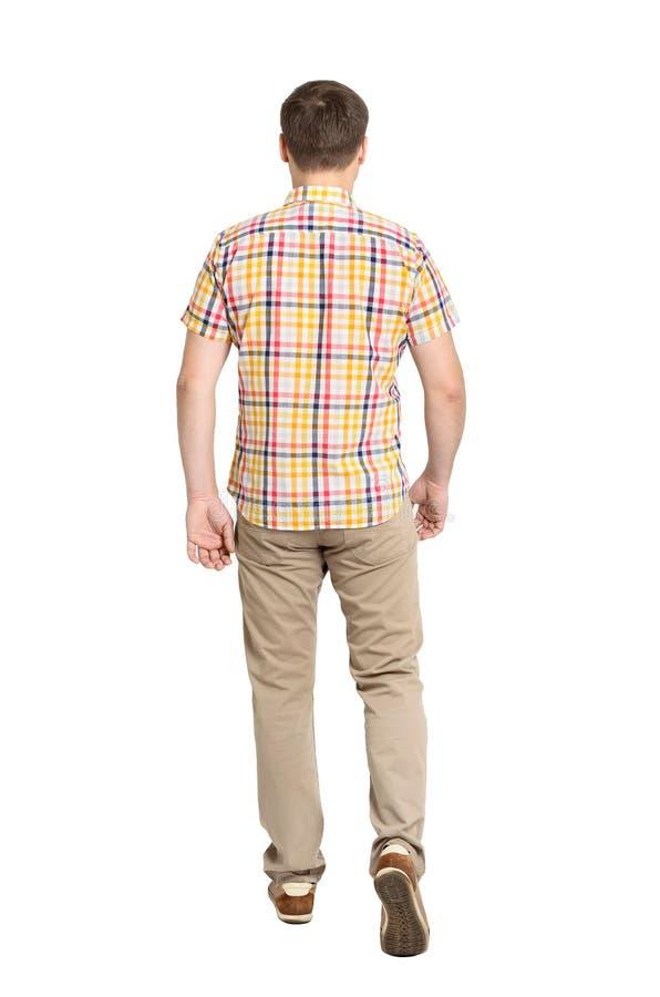 Opinión posterior el hombre hermoso que va en vaqueros y una camisa fotografía de archivo