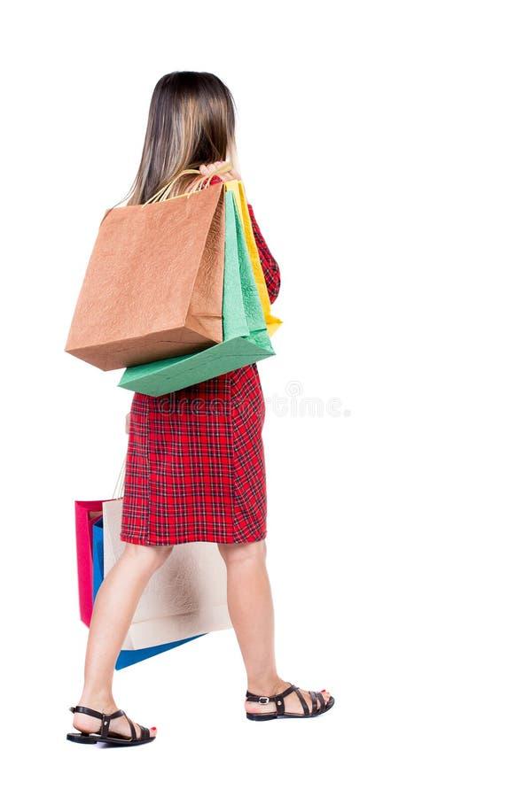 Opinión posterior la mujer que va con los bolsos de compras Muchacha hermosa i foto de archivo