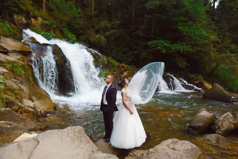 Opinión romántica que sorprende la novia feliz con el novio cerca de la cascada magnífica hermosa en montaña Vestido de boda lujo foto de archivo