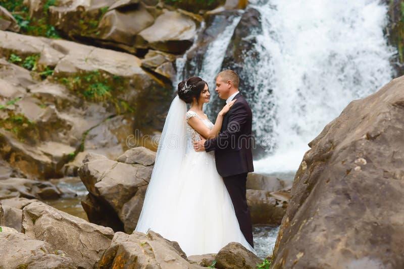 Opinión romántica que sorprende la novia y el novio felices cerca de la cascada magnífica hermosa en montaña Vida del éxito Pares imagen de archivo libre de regalías
