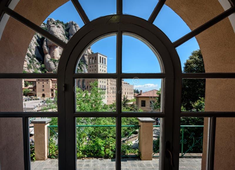 Opinión sobre edificios del monasterio viejo de Montserrat a través de la ventana del vintage fotos de archivo