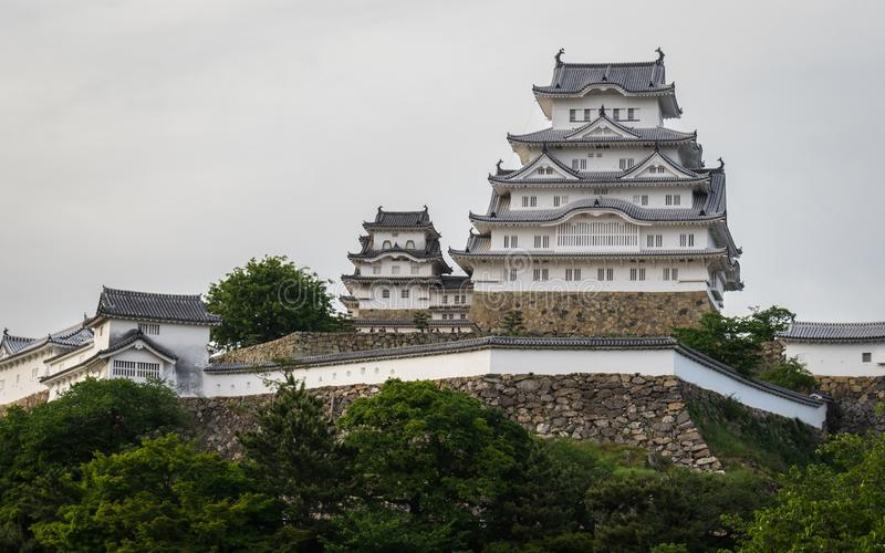Opinión sobre el castillo de Himeji en un claro, día soleado del panorama con muchos alrededor verdes Himeji, Hyogo, Jap?n, Asia imagenes de archivo