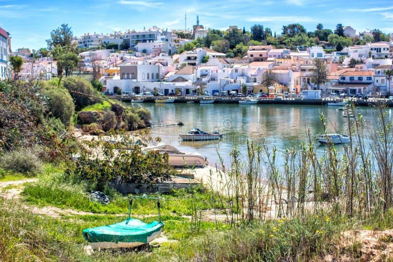 Opinión sobre el Ferragudo, Lagoa, Algarve a través del río Arade y muchos barcos de pesca en el primero plano fotos de archivo libres de regalías