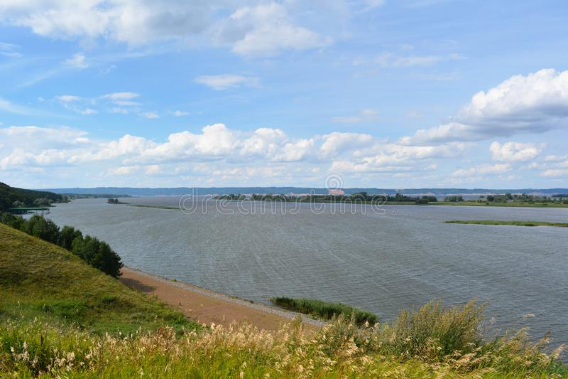Opinión sobre el río y el cielo de la colina con las hierbas salvajes en el banco fotografía de archivo libre de regalías