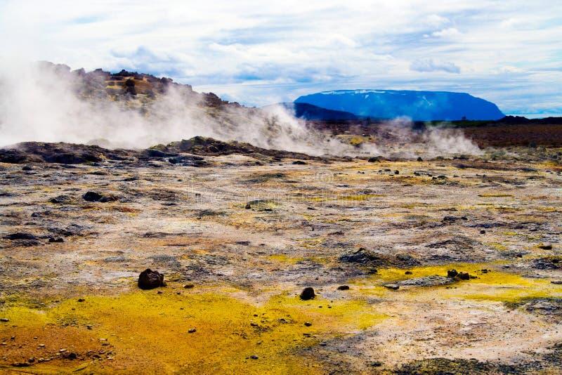 Opinión sobre el valle colorido con los depósitos amarillos del azufre en paisaje seco estéril volcánico con el fondo rojo de las imagen de archivo libre de regalías