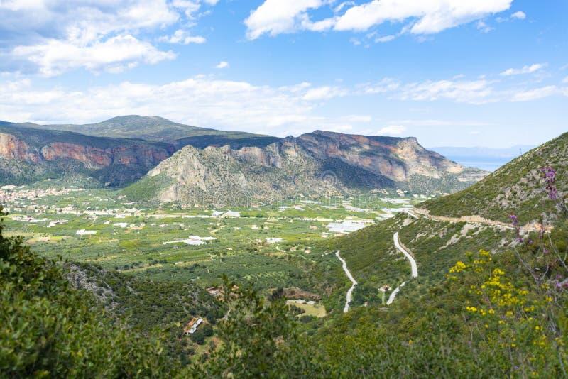 Opinión sobre el valle fértil cerca de Leonidio, Peloponeso, Grecia con la ciudad antigua, los campos y las huertas imágenes de archivo libres de regalías