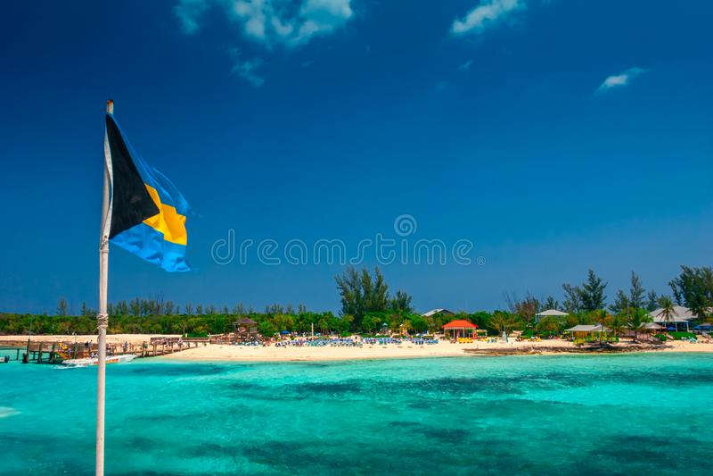Opinión sobre la isla tropical en Bahamas con la bandera nacional de Bahama imagenes de archivo