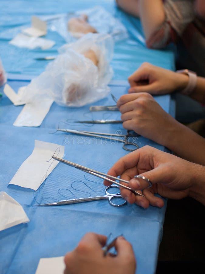 Opinión sobre la tabla con la cubierta azul y los instrumentos quirúrgicos durante curso de sutura quirúrgico fotografía de archivo libre de regalías