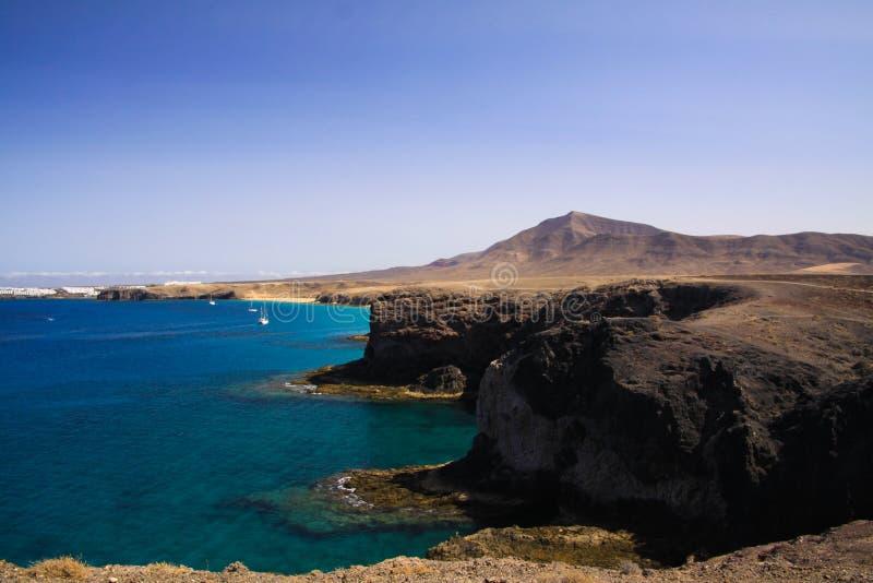 Opinión sobre los acantilados rugosos escarpados de la costa de Punta del Papagayo, Blanca de Playa - Lanzarote fotos de archivo