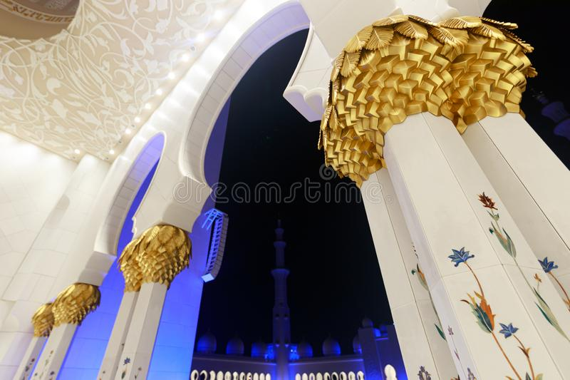 Opinión sobre los arcos de Sheikh Zayed Grand Mosque con las columnas de mármol adornadas con las imágenes del oro y de los mosai imagen de archivo libre de regalías