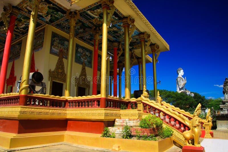 Opinión sobre pilares de oro, el tambor y la estatua blanca de Buda contra el cielo azul en el templo budista - Wat Ek Phnom, cer imagenes de archivo