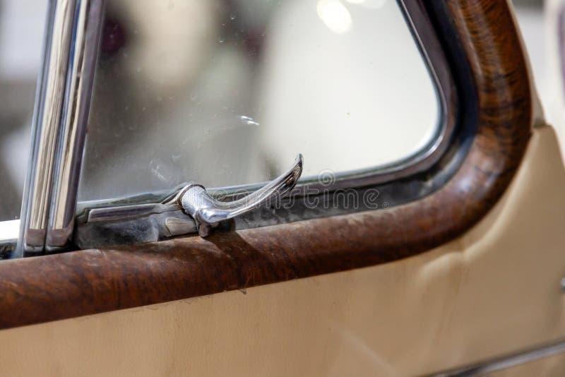Opinión sobre puerta principal abierta con la manija del cromo para abrir la ventana de la esquina del coche ruso viejo de la cla imágenes de archivo libres de regalías