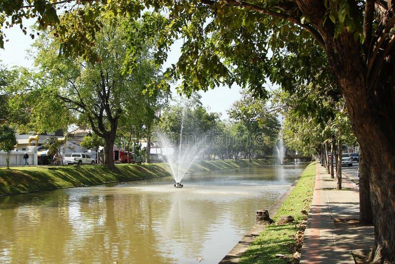 Opinión sobre un canal con las fuentes, los árboles grandes y las calles en los bancos imagen de archivo libre de regalías
