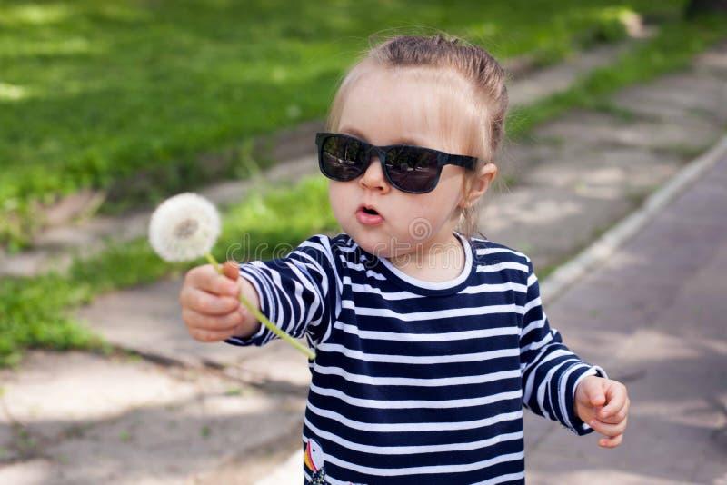 Opinión sobre una pequeña niña pequeña linda en gafas de sol en el parque de la ciudad en un día de verano soleado foto de archivo libre de regalías