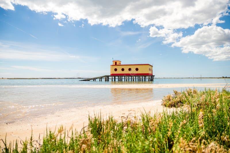 Opinión soleada de la playa del edificio histórico del salvavidas en Fuseta, parque de Ria Formosa Natural, Portugal fotografía de archivo libre de regalías