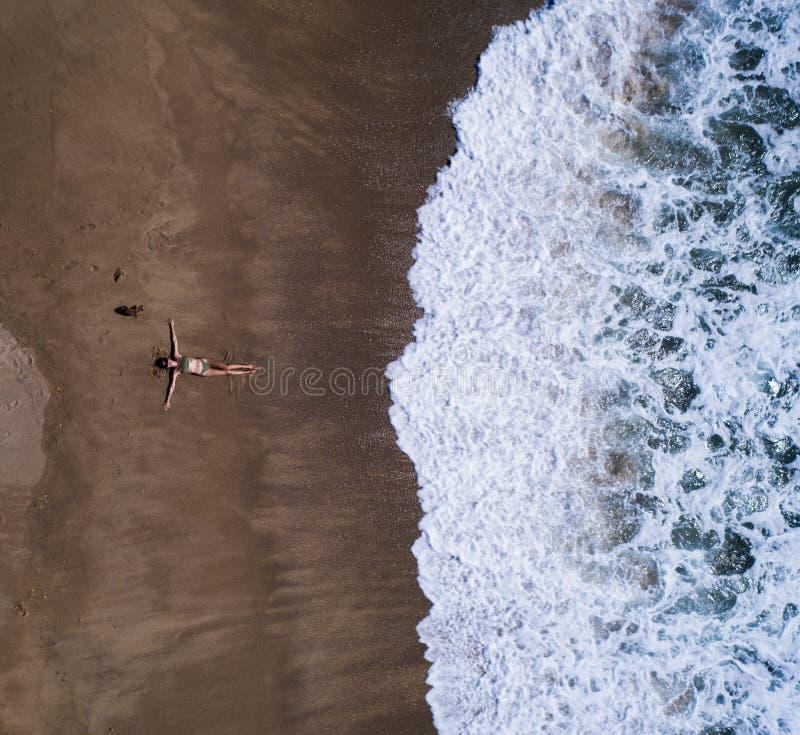 Opinión superior aérea la mujer con su colocación extendida de las manos en la playa arenosa fotografía de archivo libre de regalías