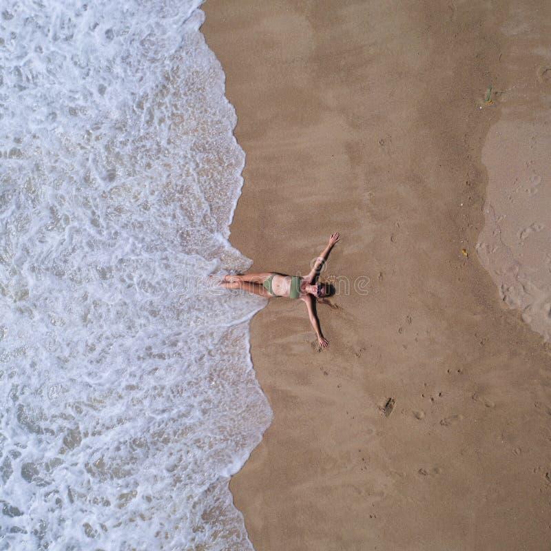 Opinión superior aérea la mujer con su colocación extendida de las manos en la playa arenosa imagenes de archivo