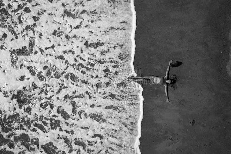 Opinión superior aérea la mujer con su colocación extendida de las manos en la playa arenosa imagen de archivo