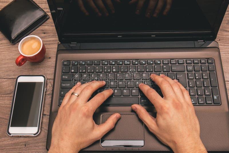 Opinión superior alguien que trabaja en un ordenador portátil, con un teléfono celular, y café del café express imagen de archivo