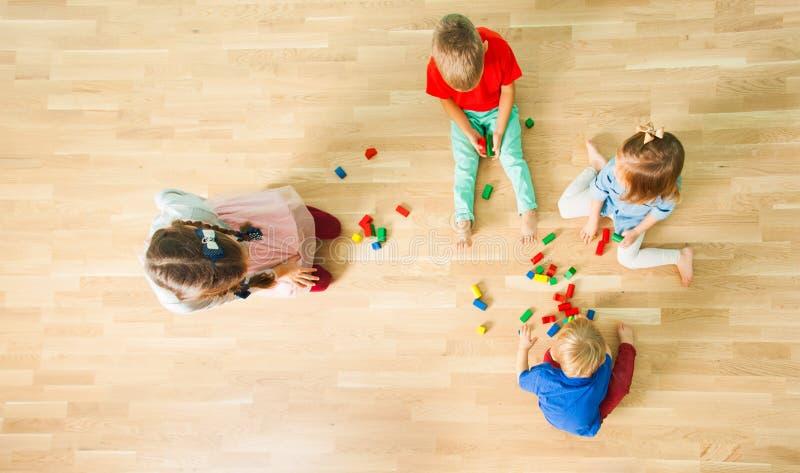 Opinión superior cuatro niños que construyen de bloques de madera fotografía de archivo libre de regalías