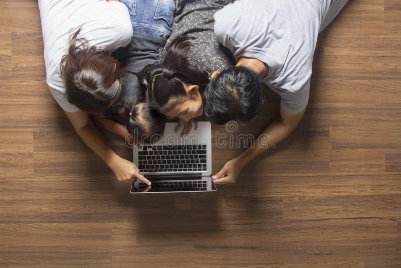 Opinión superior de la familia que miente en piso usando el ordenador portátil foto de archivo