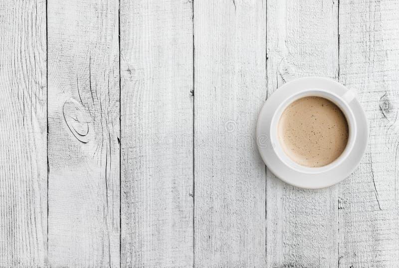 Opinión superior de la taza de café sobre el fondo de madera blanco de la tabla fotografía de archivo libre de regalías