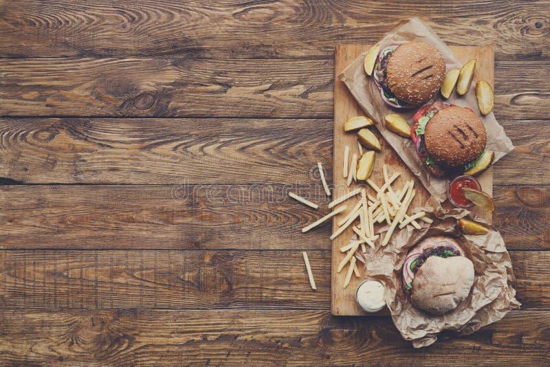 Opinión superior de los alimentos de preparación rápida sobre la madera Hamburguesas y fritadas foto de archivo libre de regalías