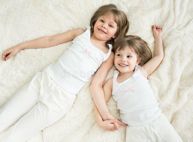 Opinión superior de mentira feliz de las pequeñas hermanas fotografía de archivo libre de regalías
