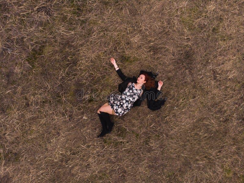 Opinión superior del abejón aéreo una muchacha que miente en un campo que se relaja y que baila Llevar un vestido con las medias imagen de archivo libre de regalías