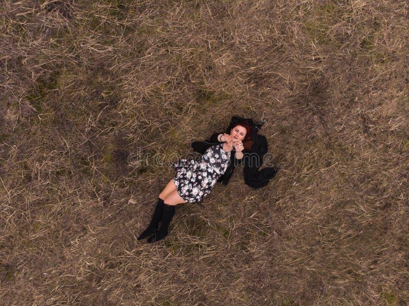 Opinión superior del abejón aéreo una muchacha que miente en un campo que se relaja y que baila Llevar un vestido con las medias foto de archivo libre de regalías