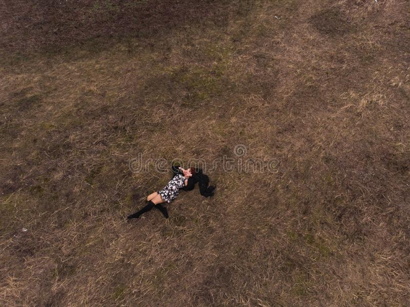 Opinión superior del abejón aéreo una muchacha que miente en un campo que se relaja y que baila Llevar un vestido con las medias fotos de archivo