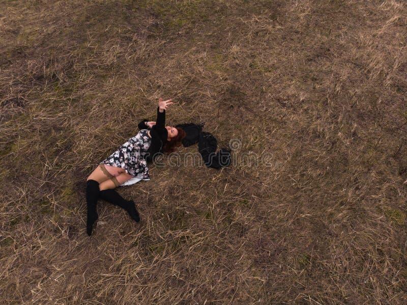 Opinión superior del abejón aéreo una muchacha que miente en un campo que se relaja y que baila Llevar un vestido con las medias foto de archivo
