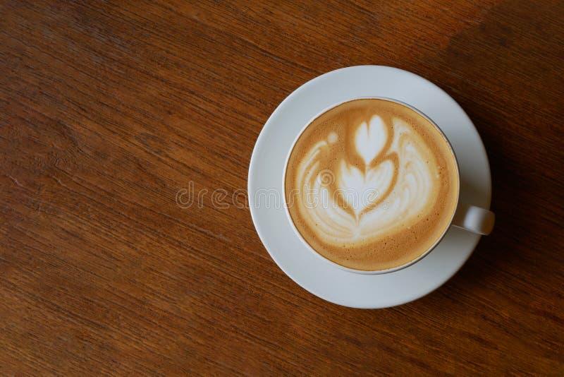 Opinión superior del café del capuchino del arte caliente del latte sobre backgroud de madera oscuro foto de archivo