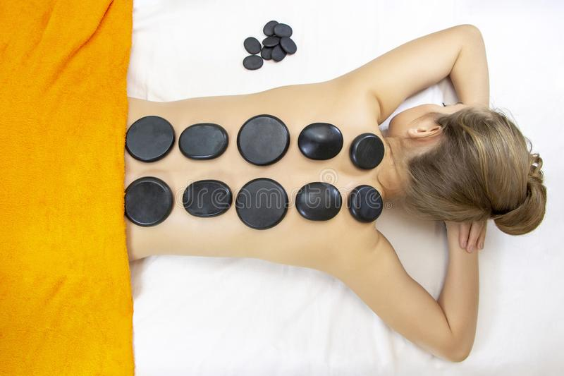 Opinión superior del masaje de la piedra la mujer joven hermosa que miente en frente con las piedras del balneario en ella detrás foto de archivo