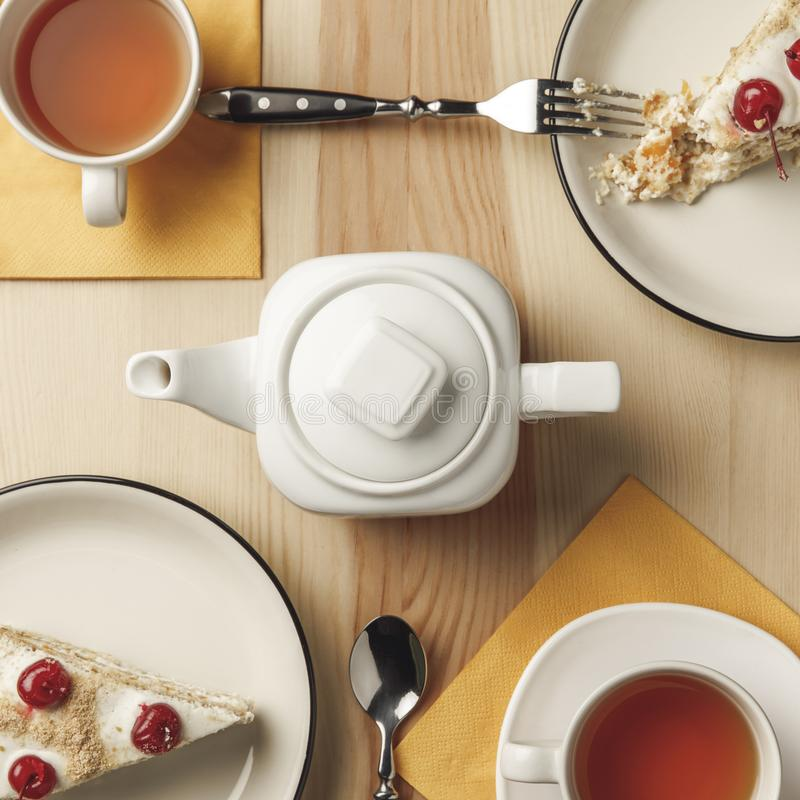 opinión superior del primer de la caldera, de dos tazas con té caliente y de pasteles deliciosos foto de archivo libre de regalías