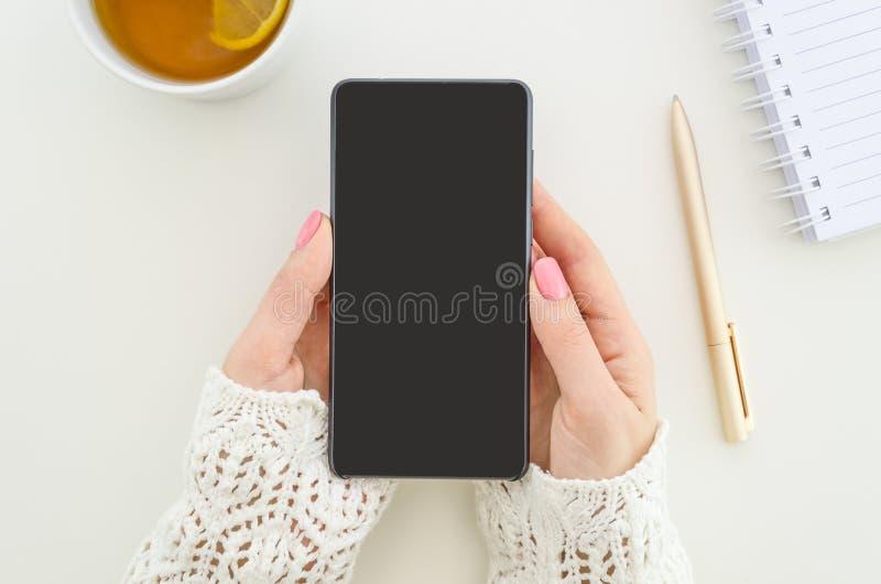 Opinión superior del smartphone ascendente falso La mujer del estudiante se sostiene con smartphone de dos manos Lugar de trabajo imagenes de archivo