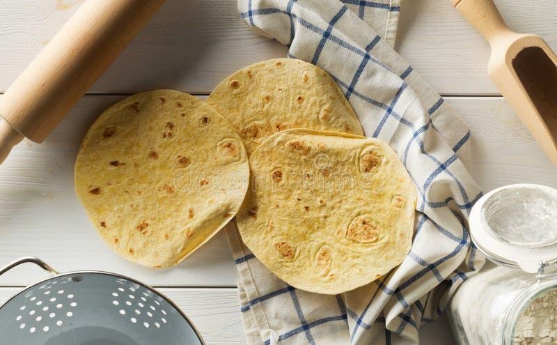 Opinión superior del trigo de la tortilla de la endecha fresca, vacía del plano sobre la paño de cocina en la tabla de madera rús foto de archivo libre de regalías