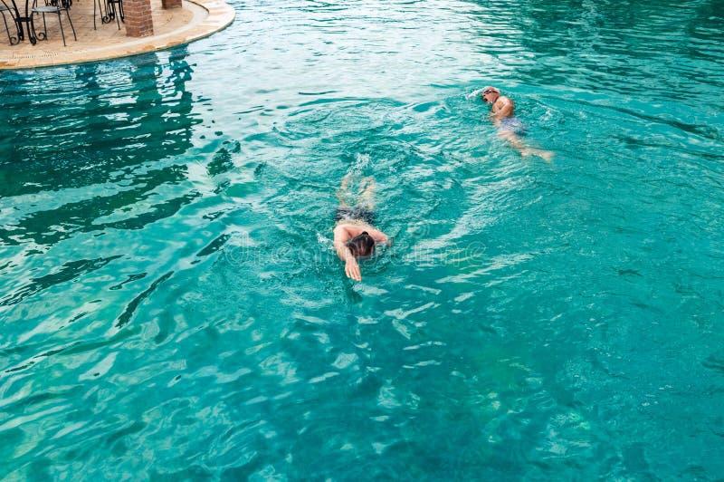 Opinión superior dos hombres caucásicos que nadan arrastre delantero en piscina foto de archivo