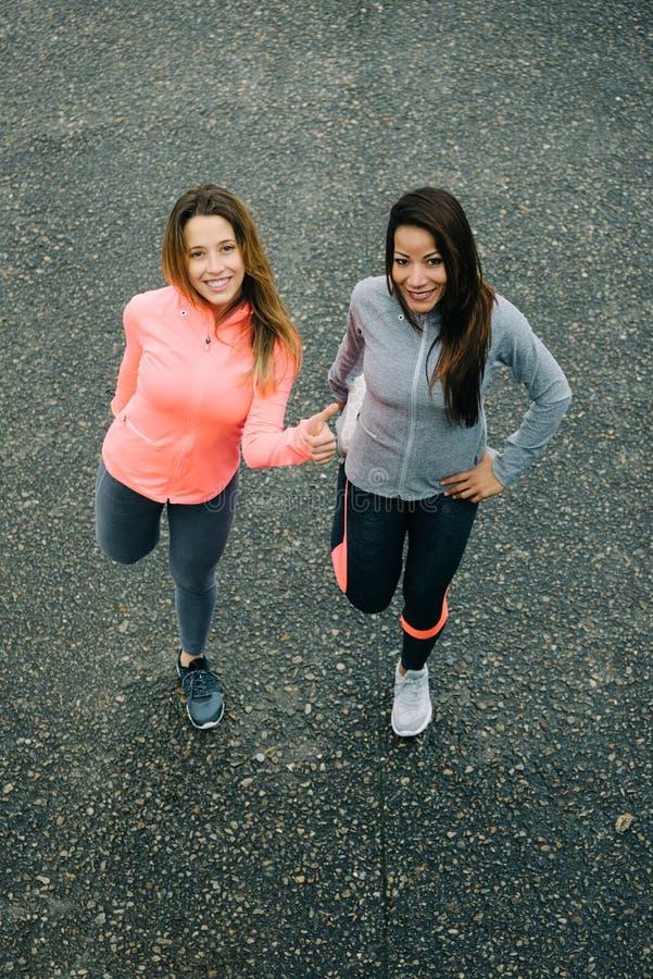 Opinión superior dos mujeres acertadas que ejercitan y que estiran imagen de archivo libre de regalías