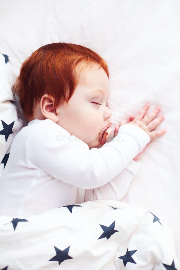 Opinión superior el bebé infantil del pelirrojo que duerme pacífico en cama foto de archivo libre de regalías