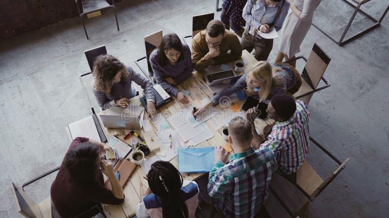 Opinión superior el equipo del negocio de la raza mixta que se sienta en la tabla en la oficina y el trabajo del desván El encarg imagen de archivo libre de regalías