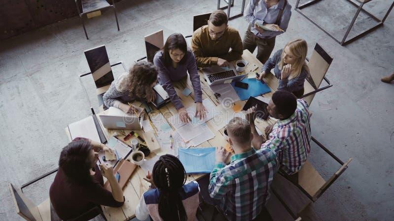 Opinión superior el equipo del negocio de la raza mixta que se sienta en la tabla en la oficina y el trabajo del desván El encarg imagenes de archivo