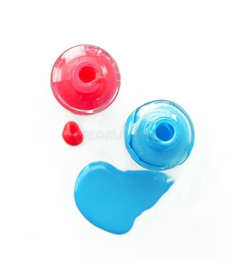 Opinión superior el esmalte de uñas mate rosado y azul en el fondo blanco imagenes de archivo