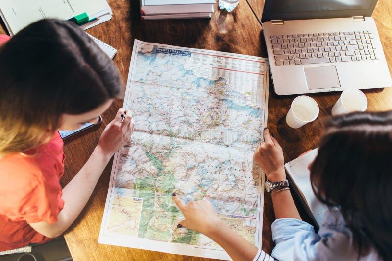 Opinión superior el grupo de estudiantes que estudian el mapa que se sienta en el escritorio fotos de archivo