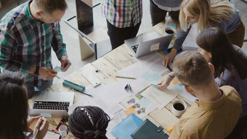 Opinión superior el grupo de personas de la raza mixta que se coloca cerca de la tabla Equipo joven del negocio que trabaja en pr imagen de archivo
