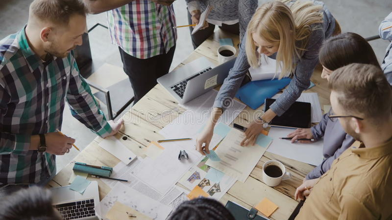 Opinión superior el grupo de personas de la raza mixta que se coloca cerca de la tabla Equipo joven del negocio que trabaja en pr foto de archivo