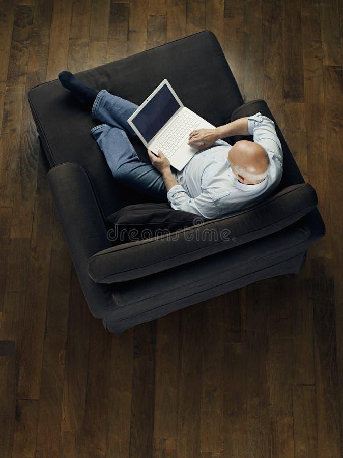 Opinión superior el hombre calvo que usa el ordenador portátil en el sofá imagen de archivo libre de regalías