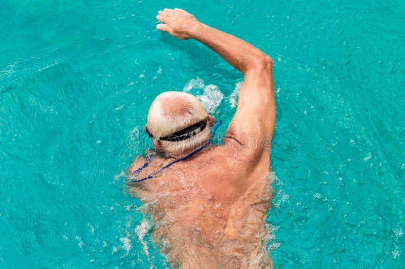 Opinión superior el hombre caucásico joven que nada arrastre delantero en una piscina imagen de archivo libre de regalías
